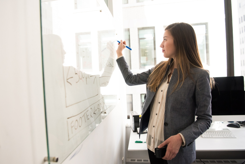 Woman-wearing-gray-blazer-writing-on-dry-erase-board-1181534